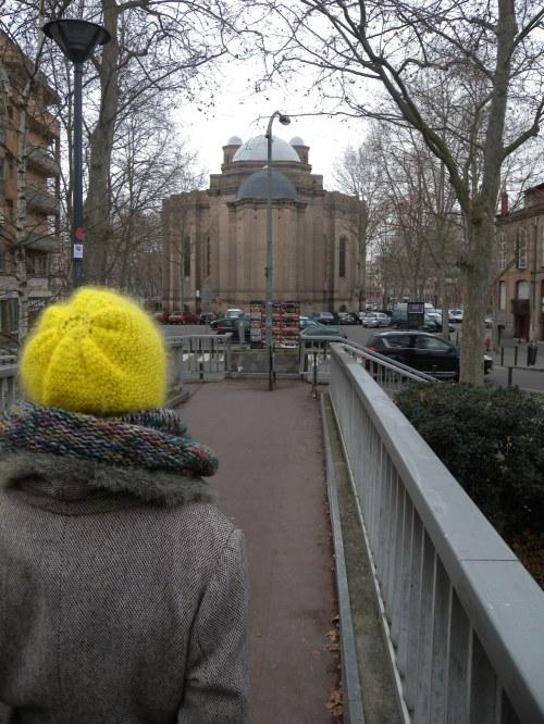 Une femme marche sur la passerelle menant à l'église saint-Aubin
